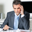 Tensed Businessman Sitting At Desk - Stock Photo