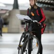 Female Cyclist With Courier Bag And Package On Street - Foto Stock