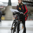 Female Cyclist With Courier Bag And Package On Street - 
