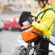 Stock Photo: Young Male Cyclist Putting Package In Courier Bag