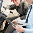 Stock Photo: Supervisor And Forklift Driver Using Laptop
