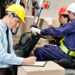 Foto Stock: Male Supervisor Writing On Clipboard At Warehouse