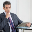Contemplative Businessman Using Digital Tablet In Office — Stock Photo