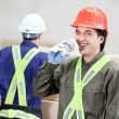 Stock Photo: Foreman Drinking Coffee While Colleague Working At Warehouse