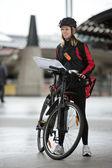 Ciclista femmina con corriere borsa e pacchetto sulla strada — Foto Stock
