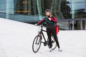 与使用对讲机的信使传递袋骑单车的女子 — 图库照片