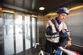Asansörde cep telefonuyla kurye çantası ile erkek bisikletçi — Stok fotoğraf