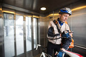 Male Cyclist With Courier Bag Using Mobile Phone In An Elevator — Stock Photo