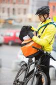 молодые мужчины велосипедист, поставив пакет в курьерская сумка — Стоковое фото