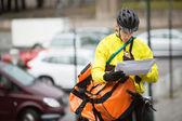 Paket ve kurye çantası caddesi üzerinde erkek bisikletçi — Stok fotoğraf