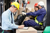 Male Supervisor Writing On Clipboard At Warehouse — Stock Photo