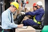 Superviseur mâle écrit dans le presse-papiers à l'entrepôt — Photo