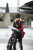 Female Cyclist With Courier Bag And Package On Street — Stock Photo