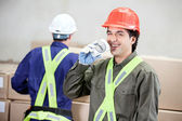 Foreman Drinking Coffee While Colleague Working At Warehouse — Stock Photo