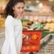 Woman With Shopping Basket Standing At Checkout Counter In Super - Stock Photo