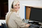 Mujer alegre mediante ordenador en recepción — Foto de Stock