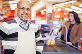 Grocery Store Cashier Standing At Checkout Counter — Stok fotoğraf