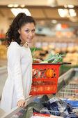 Mujer con compras de pie cesta en mostrador en super — Foto de Stock