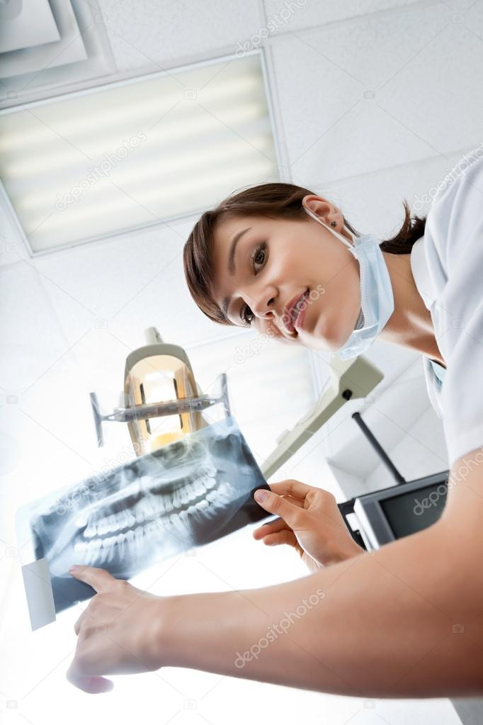 Low angle portrait of young female dentist pointing at x-ray image — Stock Photo #15854651