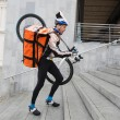 Male Cyclist With Courier Bag And Bicycle Walking Up Steps - Stock Photo