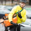 Male Cyclist With Courier Bag Using Walkie-Talkie On Street - Stock Photo