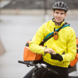 Male Cyclist With Courier Bag Using Mobile Phone On Street - Stock Photo