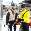 Courier Delivery Men With Bicycles Using Digital Tablet - Stock Photo