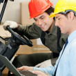 Male Supervisor And Forklift Driver Using Laptop - Stock Photo
