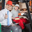 Supervisor Gesturing Thumbs Up At Warehouse — Stock Photo