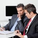Thoughtful Businessmen Using Digital Tablet At Desk — Stock Photo #16342539