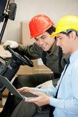 Mannelijke toezichthouder en vorkheftruck stuurprogramma met behulp van laptop — Stockfoto