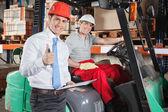 Supervisor Gesturing Thumbs Up At Warehouse — Stock Photo