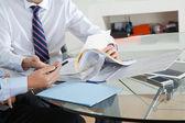 Empresario con colega discutiendo papeleo — Foto de Stock