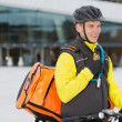 Male Cyclist With Courier Delivery Bag Using Walkie-Talkie - Stock Photo