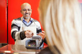 Mature Man Accepting Credit Card From Young Woman At Supermarket — Stock Photo
