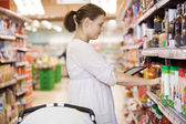 デジタル タブレットを使用してスーパー マーケットで 30 代の女性 — ストック写真