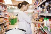 Mulher adulta meada usando tablet digital no supermercado — Foto Stock