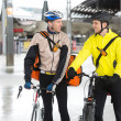 Courier Delivery Men With Bicycles Looking At Each Other - Stock Photo
