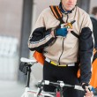 Male Cyclist With Courier Bag Using Walkie-Talkie - Stock Photo
