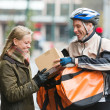 Young Woman Receiving A Package From Courier Delivery Man - ストック写真