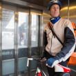 Male Cyclist With Courier Bag Riding In An Elevator - Stock Photo