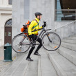 Stock Photo: Courier Delivery Man With Bicycle And Backpack Walking Up Steps