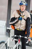 Mannelijke wielrenner met courier tas met behulp van walkie-talkie — Stockfoto