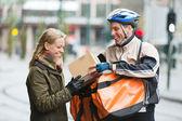 Genç kadın kurye teslimi adamdan bir paket alma — Stok fotoğraf