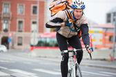 Kurye teslimi çanta binicilik bisiklet ile erkek bisikletçi — Stok fotoğraf