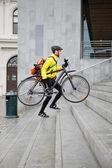 Repartidor mensajero con bicicleta y mochila subiendo pasos — Foto de Stock