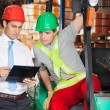 Supervisor Showing Clipboard To Forklift Driver — Stock Photo #16684301