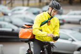 Male Cyclist With Courier Bag Using Mobile Phone On Street — Stock Photo