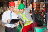 Supervisor Showing Clipboard To Forklift Driver — Stok fotoğraf