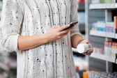 Mulher digitalização garrafa com telefone smar — Foto Stock